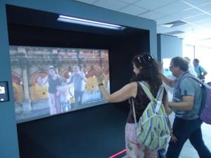 Τουρίστες_μπροστά_στην_μεγάλη_διαδραστική_οθόνη_όπου_μπορούν_να_φωτογραφηθούν_με_αξιοθέατα_του_νησιού